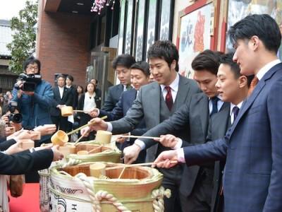 集まった歌舞伎ファンに開いたばかりの樽酒を振る舞う役者たち